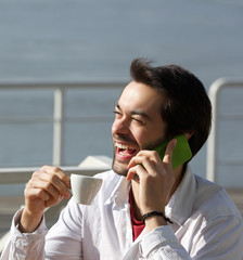 Cheerful young man drinking coffee and talking on mobile phone