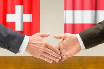 Vertreter der Schweiz und Österreichs reichen sich die Hand