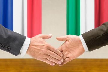 Vertreter Frankreichs und Italiens reichen sich die Hand