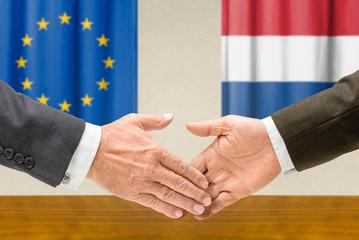 Vertreter der EU und der Niederlande reichen sich die Hand