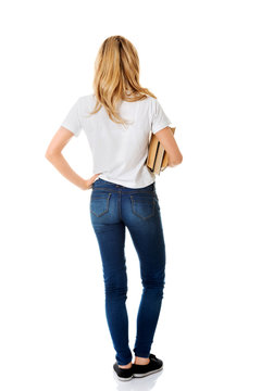 Back view of young woman holding books