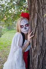 The girl in the image of Santa Muerte near the tree