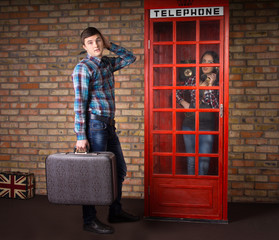 Man with Suitcase Waiting at the Telephone Booth