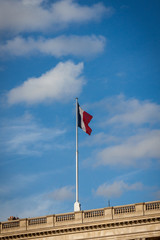 Flag of France fluttering under a serene blue sky