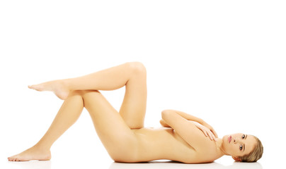 Slim naked woman lying on the floor