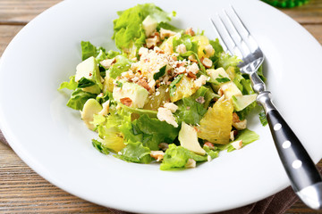 Salad with Avocado, Lettuce, Orange and Nuts on a white bowl