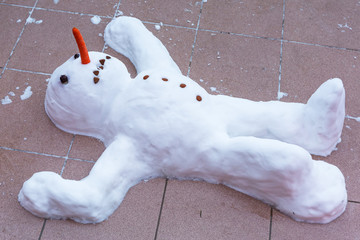 Funny snowman lying on the ground