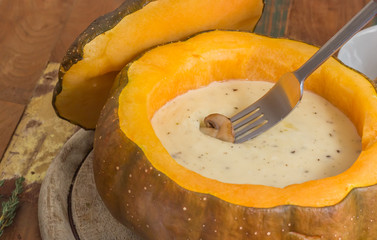 Cheese fondue in a roasted pumpkin with chestnut mushroom on a f