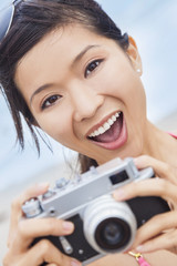 Asian Woman at Beach Taking Photograph With Camera