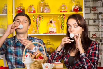 Couple Sipping a Drink From Small Cups at the Cafe