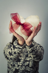 Woman hiding his face with a fabric heart. Valentine's day