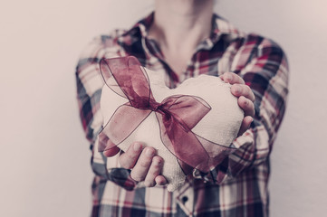 Woman in plaid shirt holding a fabric heart. Valentine's day