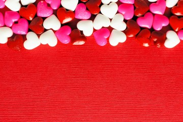 Valentines Day candy top border on a red paper background