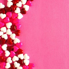 Valentines Day candy curved border on a pink paper background