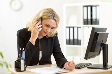 Business woman working in office. Worker talking by phone and