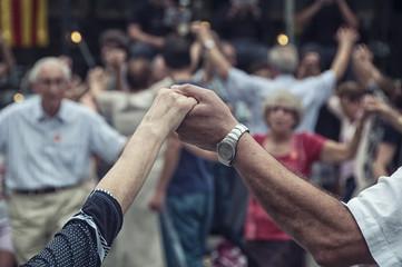 senior people holding hands and dancing national dance Sardana