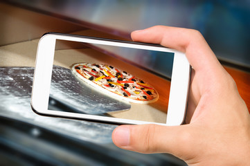 Hands taking photo pizza with smartphone