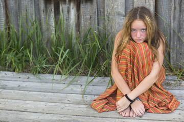 Young hippie girl sitting on the ground outdoors.