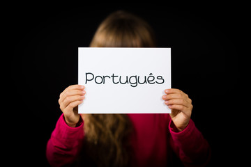 Child holding sign with Portuguese word Portugues - Portuguese i