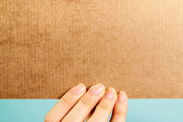 Hand holding a blank cardboard message on blue background