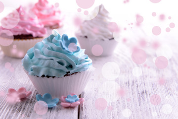 Delicious cupcakes on table on festive background