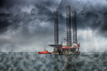 Oil Rig at sea on a dark cloudy dramatic sky.