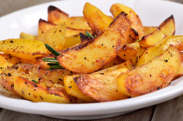 Fried potato wedges on white plate