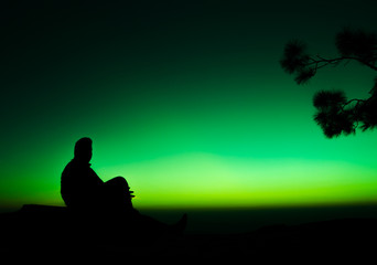 silhouette of man sitting on rock