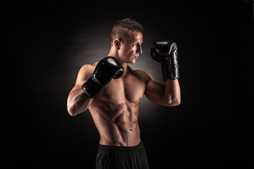 Muscular man in studio on dark background