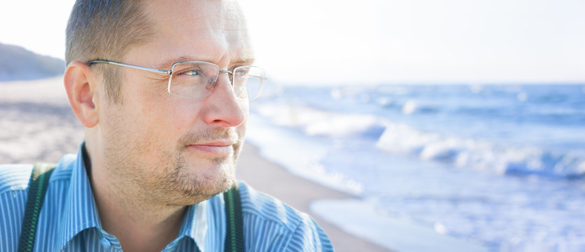 man 45 smiling glasses outdoor looking sea