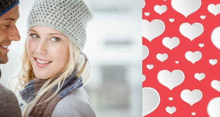 Composite image of couple in warm clothing hugging
