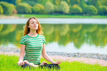 concentrated girl in lotus position doing yoga on the nature