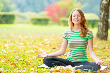 Slim beautiful girl relaxing sitting in the lotus position