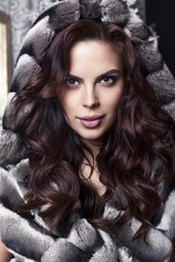 sensual woman with dark hair in luxurious fur coat