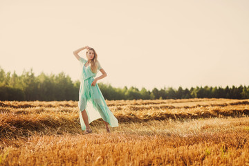 young and pretty woman on golden cereal field in summer
