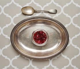Jar of glaced cherries on a vintage platter