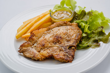 Pork steak with french fries and salad on a white background.