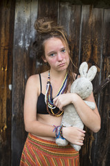 Sad teen girl with old toy rabbit in the hands of the outdoors.
