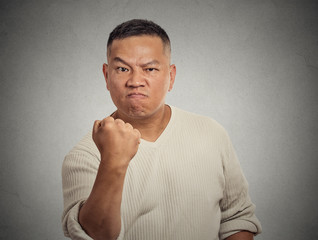 angry middle aged man showing fist isolated on grey background
