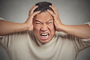 headshot stressed guy screaming on grey wall background