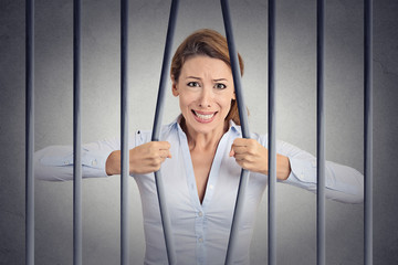 Stressed desperate angry woman bending bars of her prison