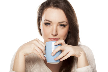 positive young woman holding a cup of tea