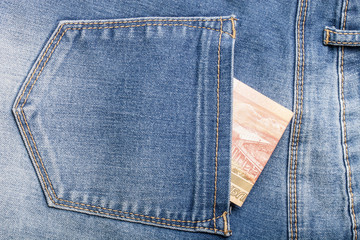 The pocket of jeans with money. Cloth background