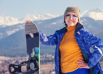 Woman with snowboard on the snow hill