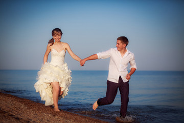 happy bride and groom running along the beach