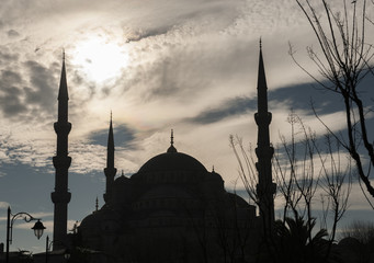 Silhouette of mosque against cloudy sky