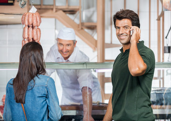 Happy Man On Call While Woman Buying Meat