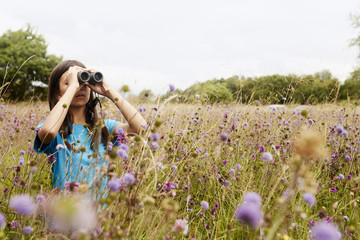 Girl standing in meadow, looking through binoculars