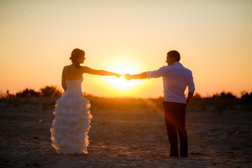 happy newlyweds at sunset