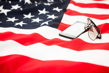 Black smartphone and glasses are on the US flag